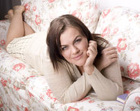 Portrait of beauty smiling woman with book reading on sofa Royalty Free Stock Images