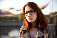 Autumn portrait in park of red-haired girl in sunset light. Portrait of Beauty Teenage Model Girl with Red Hair on the Background of Nature on the Field in Sun Royalty Free Stock Photography