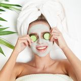 Portrait of beauty woman laying with towel on the head, cucumber on her eyes, facial mask. Spa therapy. Relax. White background royalty free stock photography
