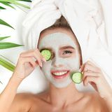 Portrait of beauty woman laying with towel on the head, cucumber on her eyes, facial mask. Spa therapy. Relax. White background stock photography