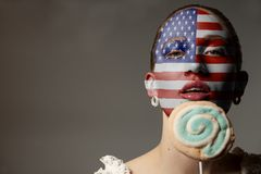 Portrait Beauty Woman with painted USA flag holding Colorful lollipop. On gray background stock photo