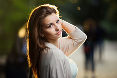 Portrait of beauty woman with perfect smile walking on the street and looking at camera, sunset light Royalty Free Stock Photo