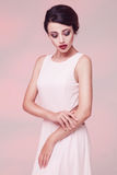 Portrait of beauty woman in white dress. Isolated over light pink studio background Stock Photos