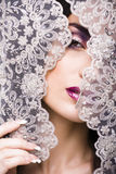 Portrait of beauty young woman through lace Stock Photography