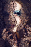 Portrait of beauty young woman through lace close up mistery mak Royalty Free Stock Image