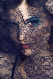 Portrait of beauty young woman through lace close up mistery makeup Royalty Free Stock Photos