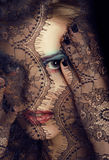 Portrait of beauty young woman through lace close up mistery makeup Stock Photo