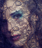 Portrait of beauty young woman through lace close up mistery makeup Royalty Free Stock Image