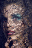 Portrait of beauty young woman through lace close up mistery makeup Stock Images
