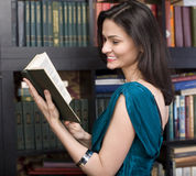 Portrait of beauty young woman reading book in library Stock Photography