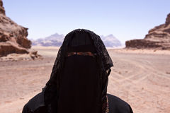 Portrait of Bedouin woman with burka in desert. Bedouin woman dressed in Traditional burka standing alone in the the desert of jordan called wadi rum, the Royalty Free Stock Image