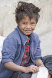 Portrait beggar boy begs for money from a passerby in Leh. Ladakh, India. LEH, INDIA - SEPTEMBER 08 2014: Unidentified beggar boy begs for money from a passerby Stock Images