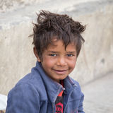 Portrait beggar boy begs for money from a passerby in Leh. Ladakh, India. LEH, INDIA - SEPTEMBER 08 2014: Unidentified beggar boy begs for money from a passerby Stock Photos