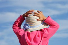 Portrait from behind of cute baby catching flying straw hat. Pink-dressed toddler is trying to catch her little straw hat in windy environment Stock Photos