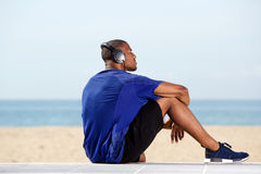 Fit african man listening to music at beach royalty free stock photography