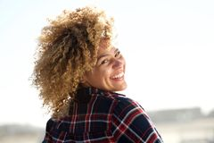 Behind of happy young woman with curly hair turning around royalty free stock photography