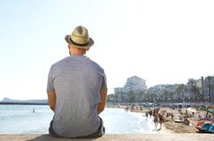 Portrait from behind of a man sitting alone looking at the beach Stock Photography