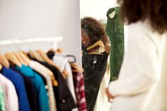 Behind of smiling young african woman looking in a mirror and tries a new dress stock photo