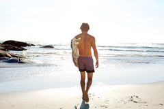 Portrait from behind of surfer walking to the ocean Stock Image