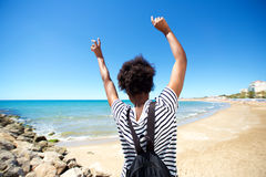 Behind of young black woman enjoying on the beach with her hands raised royalty free stock images