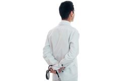 Portrait from behind of young brunette man doctor in unifrom with stethoscope in his hands isolated on white background Stock Photography