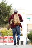 Behind of young man walking outdoors with bag and skateboard. Portrait from behind of young man walking outdoors with bag and skateboard Stock Image