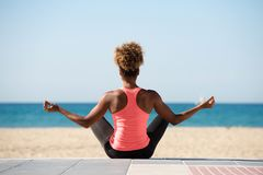 Behind of young woman doing yoga exercise on seaside Royalty Free Stock Images