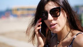 Portrait, belle fille, femme en verres de soleil parlant à un téléphone portable sur la plage, un jour chaud d'été, banque de vidéos