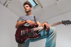 Portrait from below upward of young guitarist looking away Royalty Free Stock Image