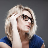 Portrait of woman listening. Portrait of bespectacled woman listening but maybe also bored by the speaker on a gray background Stock Photography