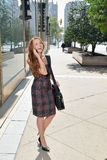 Portrait of beuatiful young business woman with red hair. Beautiful young business woman or student with red hair stands city street holding brief case, talking Royalty Free Stock Image
