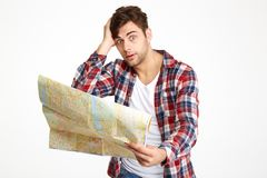 Portrait of a bewildered young man holding travel map Royalty Free Stock Photos