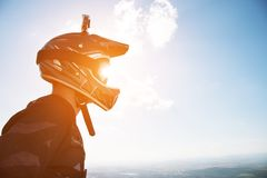 Portrait of a bicyclist in a full-face helmet and sunglasses against a background of a mountain. That is hidden behind a low cloud cover Royalty Free Stock Photography