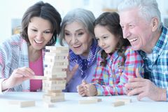 Portrait of big family with cute little girl playing. Big family with cute little girl playing with wooden blocks together royalty free stock photography