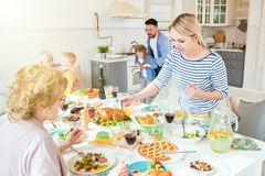 Big Family Together. Portrait of big happy family enjoying time together in dining room, focus on two women at festive dinner table in modern sunlit apartment royalty free stock images