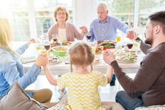 Family Praying at Family Dinner. Portrait of big happy family saying grace at dinner holding hands during festive celebration in sunlight Royalty Free Stock Photo