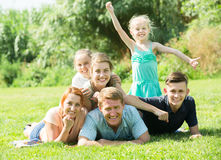 Portrait of big modern family with parents and four children lying on green lawn outdoors royalty free stock image