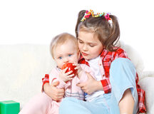 Portrait of a big sister feeds the younger apple Royalty Free Stock Photography
