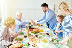Family Enjoying Festive Dinner in Sunlight. Portrait of big two generation family enjoying dinner together sitting round festive table with delicious dishes stock photos