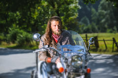 Portrait of biker man with beard sitting on his motorcycle. Portrait of biker with long hair and beard in a leather jacket and sunglasses sitting on his bike Royalty Free Stock Photography