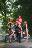 Portrait of biker and three sexy girls Royalty Free Stock Photography