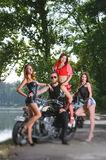 Portrait of biker and three sexy girls. Man wearing sunglasses and sitting on his cruiser motorcycle. Beautiful fashion women posing in sexy clothes near the Stock Photo