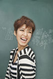 Portrait of bilingual woman laughing in front of blackboard Stock Images