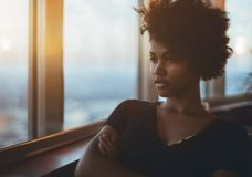 Portrait of biracial thoughtful curly girl near window. Portrait of pensive stately young black female with curly afro hair sitting in dark settings next to big royalty free stock photos