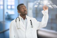 Portrait of black african american doctor with finger at medical symbols. Royalty Free Stock Photos