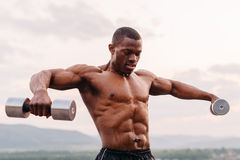 Portrait of black african american muscular man lifting dumbbells against the sunset sky background.  Royalty Free Stock Photography