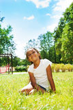 Portrait of black girl in park dreaming on lawn Royalty Free Stock Image