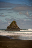 Portrait of black Karekare Beach with the Watchman Rock. Auckland, New Zealand - March 2, 2017: Portrait of black sand Karakare Beach under blue cloudy sky with Royalty Free Stock Photos