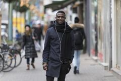 Portrait of Black Man with Earphones and Coat Posing on Sidewalk