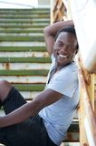 Portrait of a black man sitting on stairs and smiling outdoors Royalty Free Stock Image